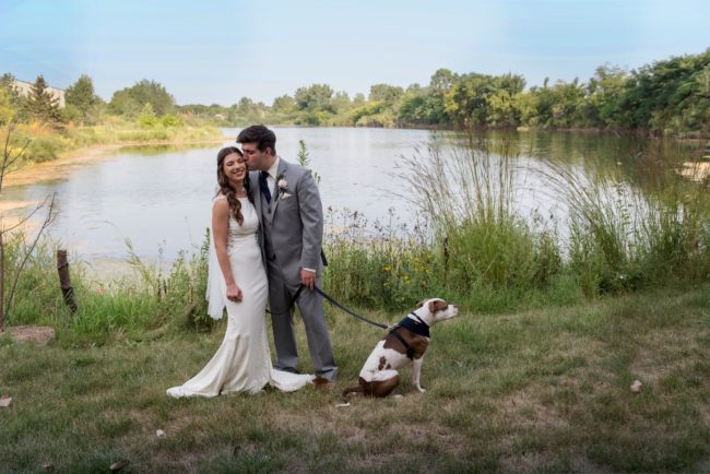 Alan gives Rachel a kiss at there wedding by a lake, while holding a dog.